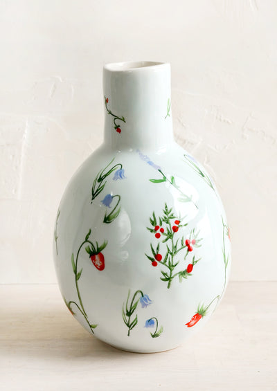 A ceramic vase with bulbous base and narrow top with painted floral print.