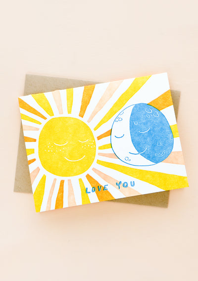"A greeting card and kraft envelope. Card features image of sun and moon with text beneath reading ""Love you"""