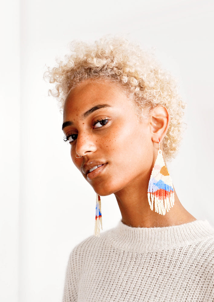 2: Model wears beaded fringe earrings and white top.