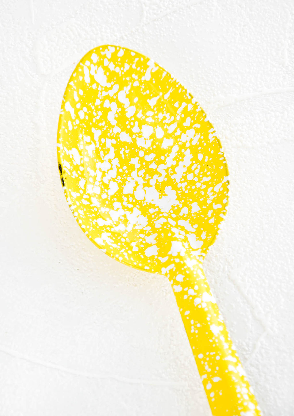 2: Metal spoon with splattered yellow and white enamel coating