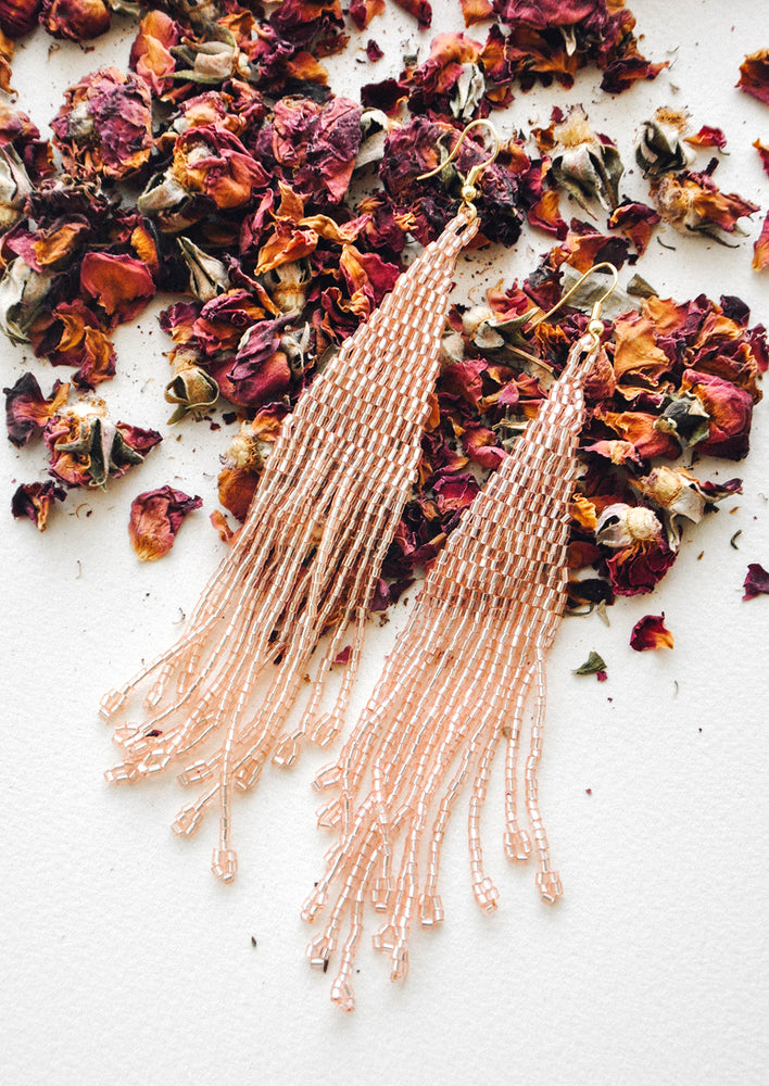 Iridescent Blush: Light pink iridescent beaded fringe earrings rest atop a bed of dried rose petals.