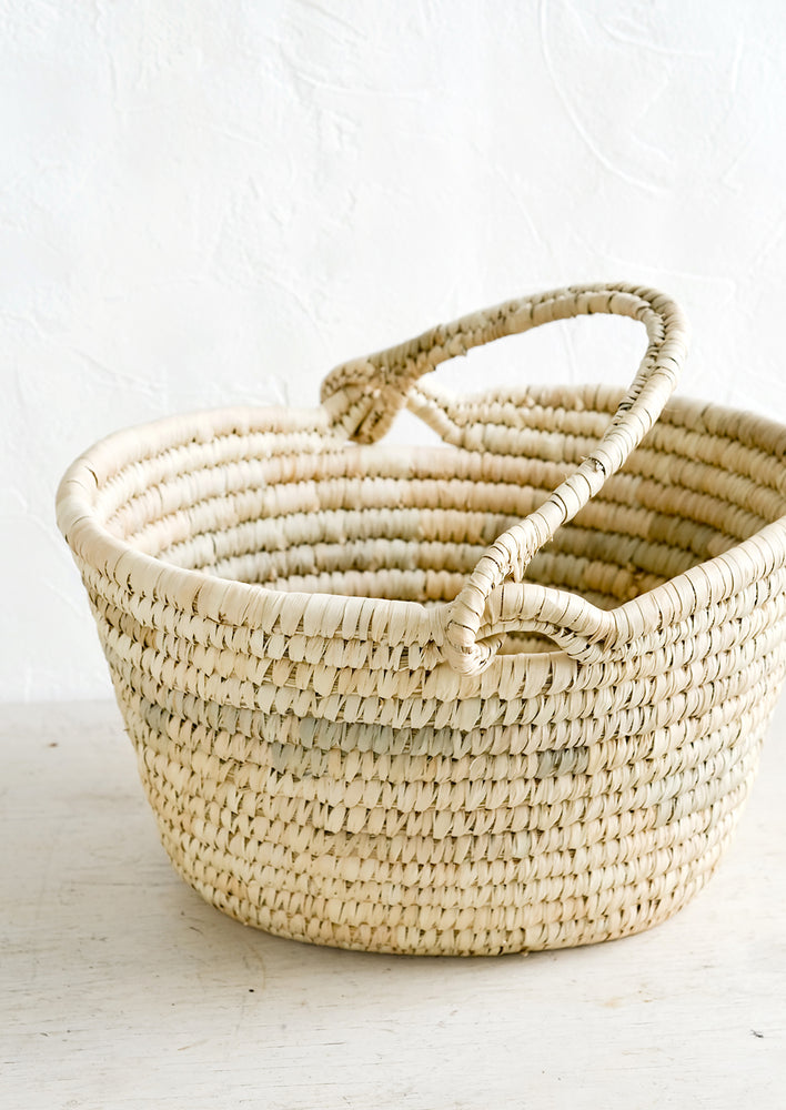 1: An oval shaped basket made from natural straw with a mobile top carrying handle.
