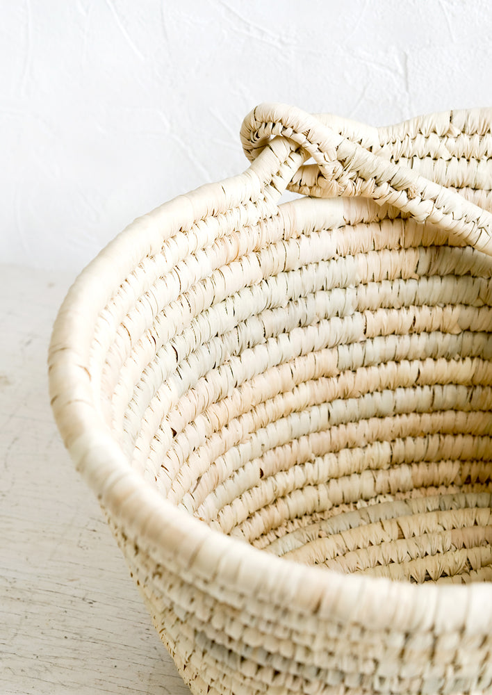2: A swing-attached carrying handle on a natural straw basket.