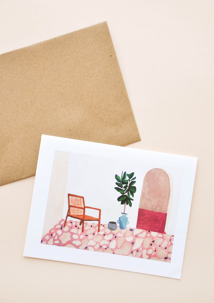 1: Greeting card with patio illustration showing a brown chair, potted plant, archway door, and pink tile floor. Shown with brown paper envelope.