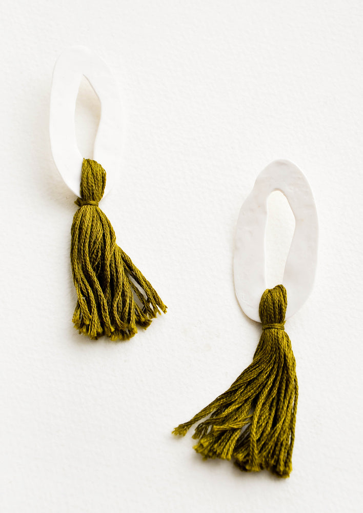 Olive: Open white oval earrings with green tassels.