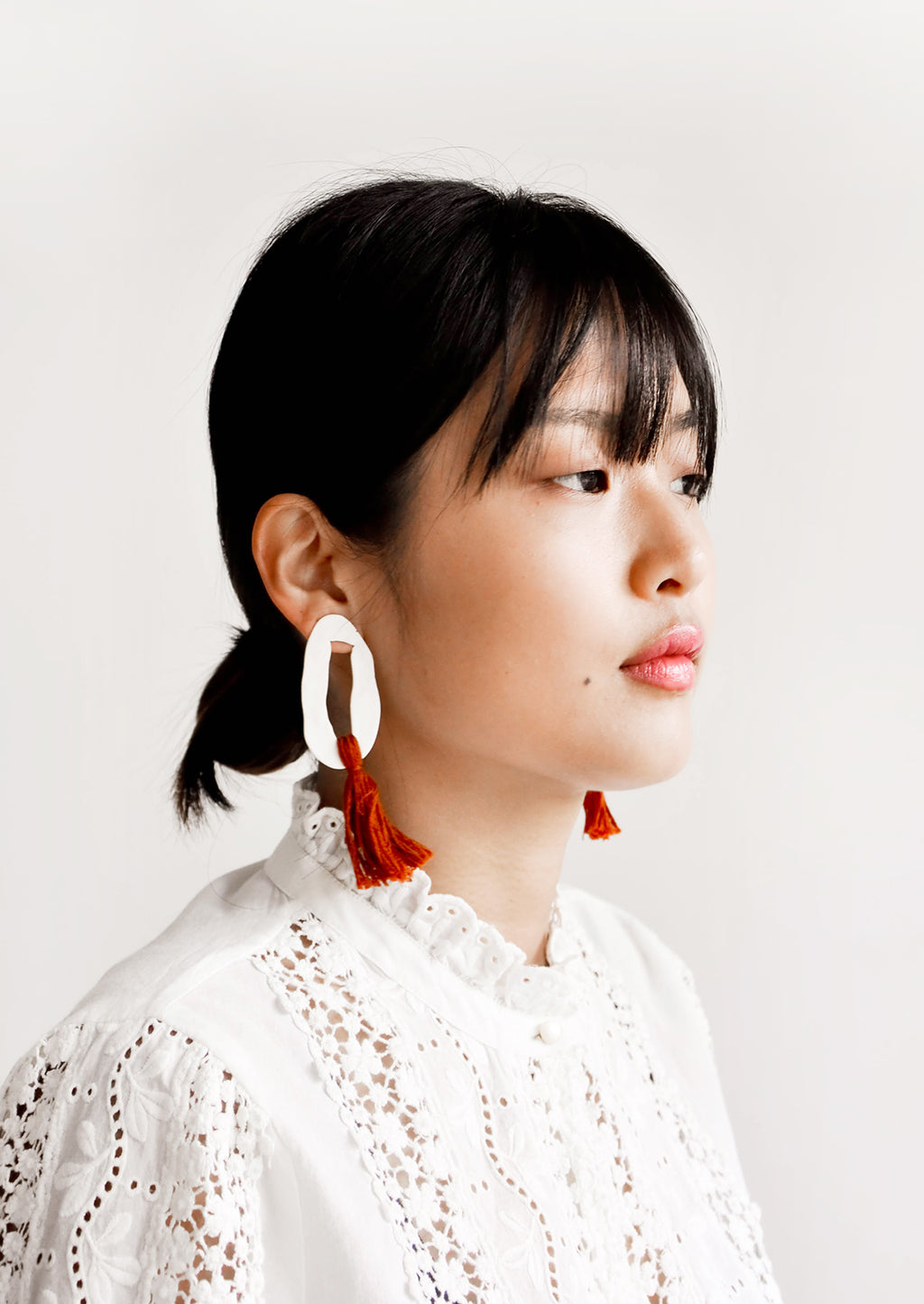 1: Model wears white and red earrings with white blouse.