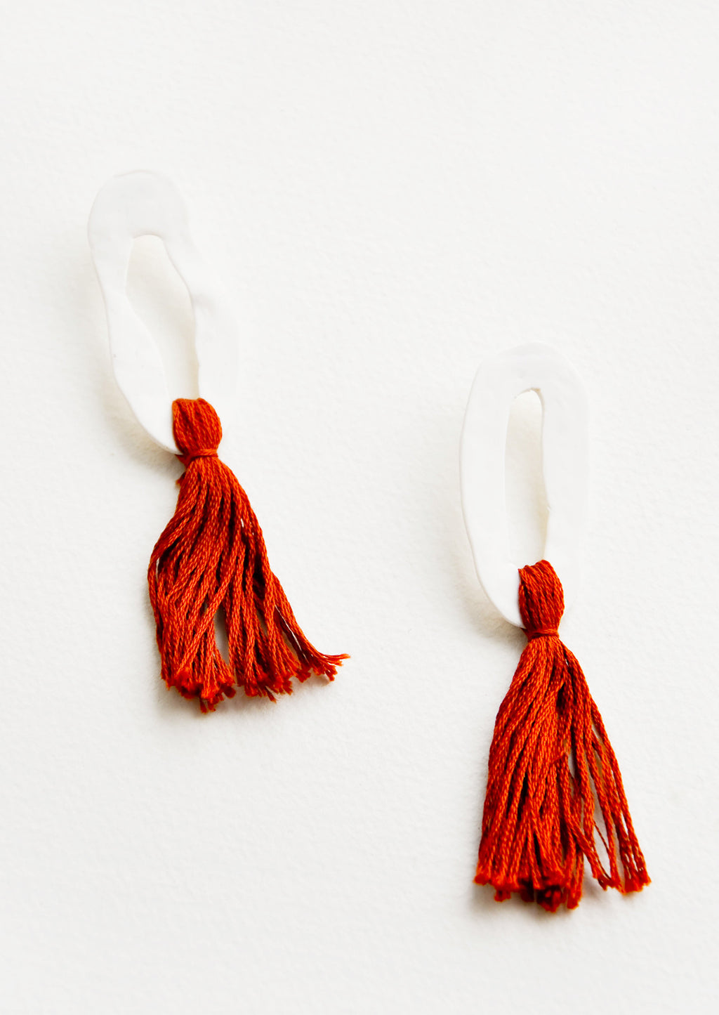 Rust: Open white oval earrings with red fringe.