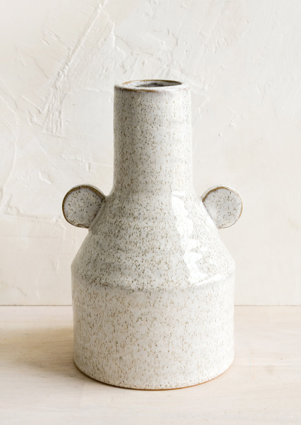 1: A ceramic vase in glossy sand speckle glaze with round decorative tabs at sides.