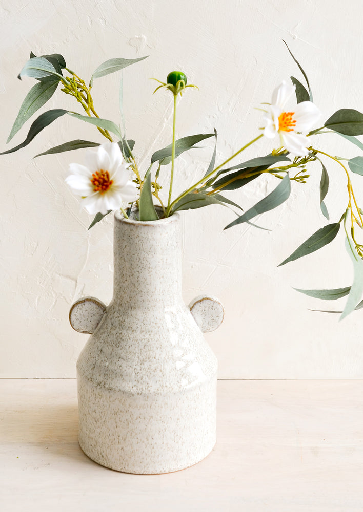 2: A speckled ceramic vase with flowers.