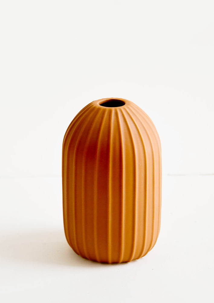 Terracotta colored ceramic vase with vertical ribbed texture and narrow opening