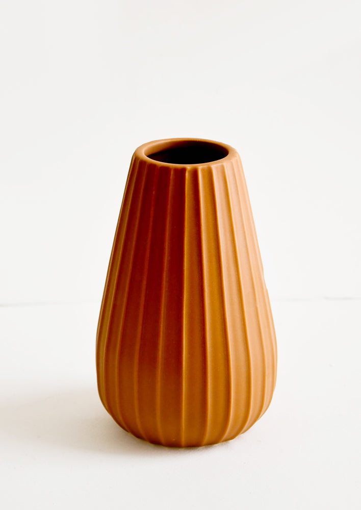 Terracotta colored ceramic vase with vertical ribbed texture and wide mouth opening