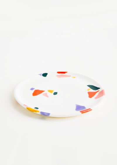 Small, plate-like ceramic dish in ivory with hand-painted, fragmented pattern in a mix of colors