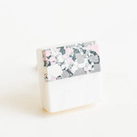 1: Square cabinet knob with white marble bottom half and splattered paint top half