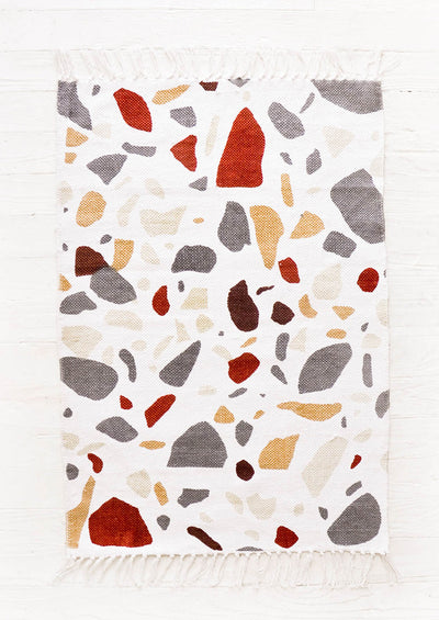 White cotton flatweave rug with allover terrazzo pattern in shades of rust, orange and grey. Fringed ends on two sides.