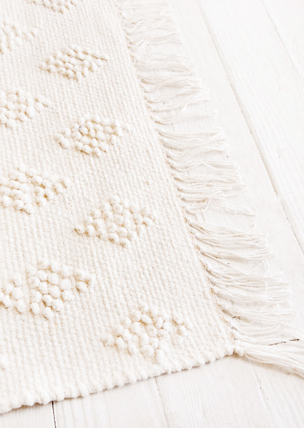 1: Flatweave rug in ivory cotton with raised, tonal textured triangle pattern and fringe trim on two ends..