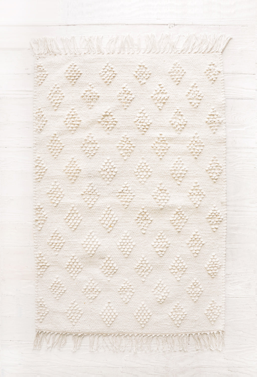 2: Flatweave rug in ivory cotton with raised, tonal textured triangle pattern and fringe trim on two ends.