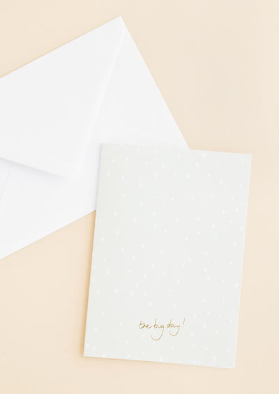 "A white envelope and a pale gray greeting card with white dots and the words ""the big day"" in small gold script at bottom center."