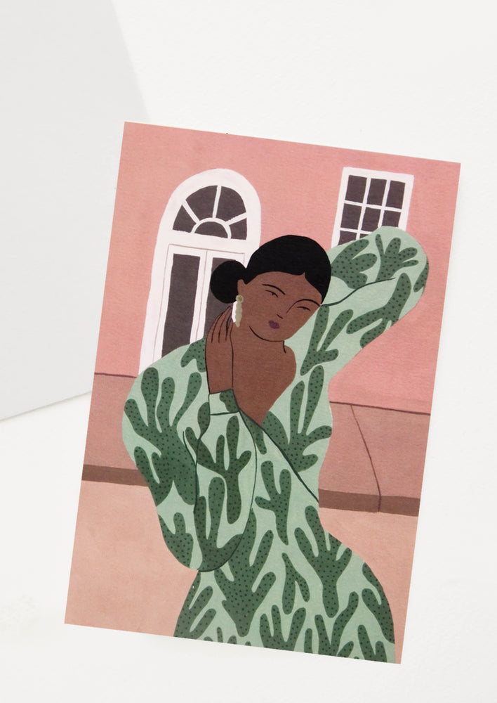 1: Oversized greeting card with woman in leaf print dress posing in front of a building