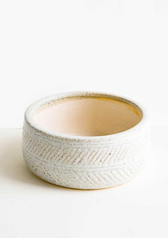 1: Shallow ceramic vessel designed for use as a planter, with herringbone textured exterior