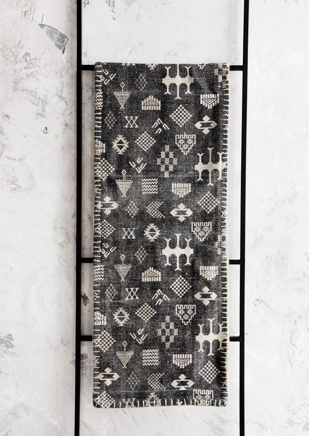 Black: Fabric table runner with tribalistic symbols printed in white on black background with whipstitched edges