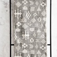 Washed Charcoal: Fabric table runner with tribalistic symbols printed in white on grey background with whipstitched edges