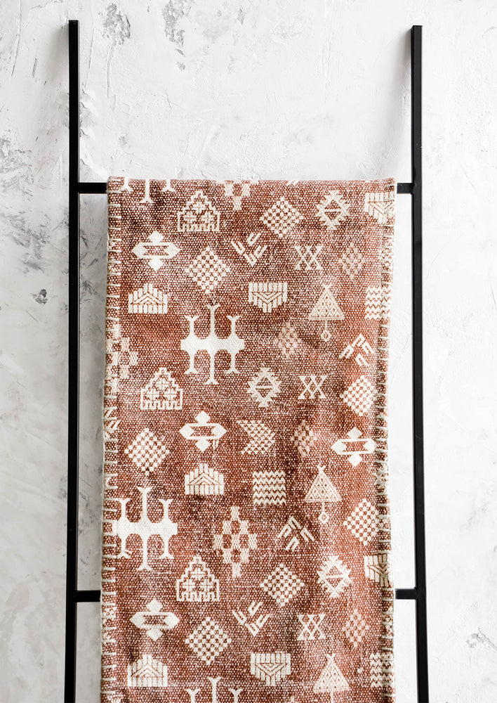 Maroon: Fabric table runner with tribalistic symbols printed in white on rust colored background with whipstitched edges