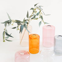 1: Multiple clear colored glass vases in a variety of colors, displayed with eucalyptus branch