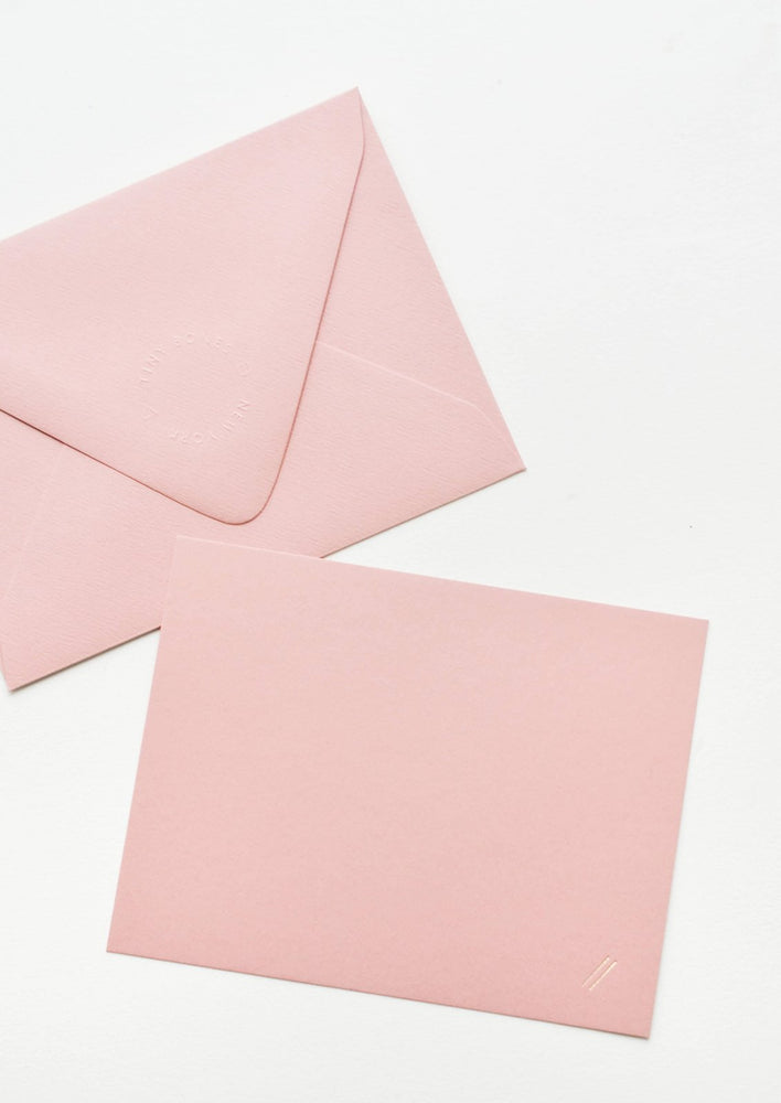 A pink envelope and pink greeting card with two small gold foil diagonal lines at bottom right.
