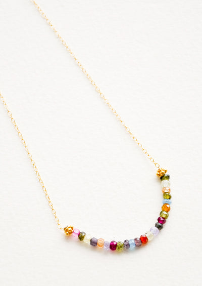 Yellow gold chain necklace with multicolored glass beads arranged in a half circle.