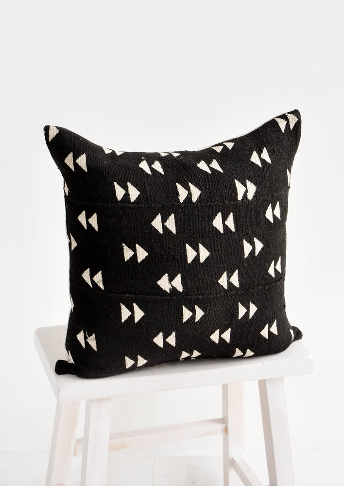 1: Square throw pillow in black mudcloth with allover tan triangle pattern