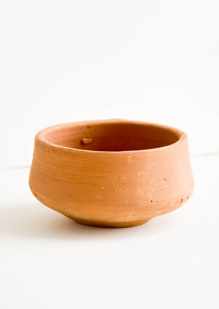 1: Round terracotta clay bowl with subtly footed silhouette