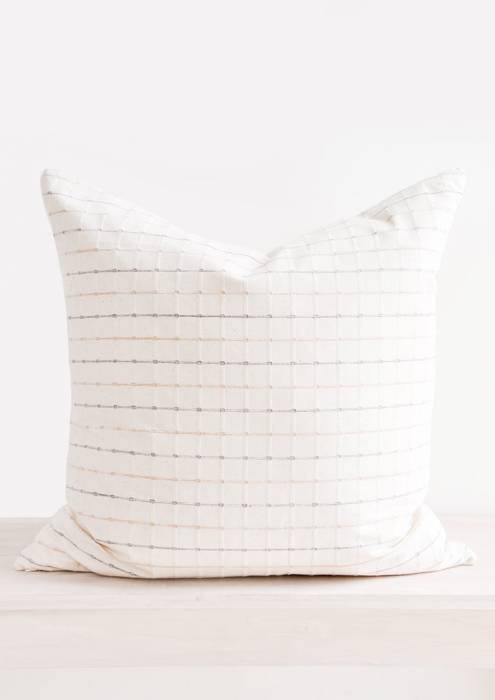 Square throw pillow in natural cotton with pastel blue and pink horizontal stripes throughout