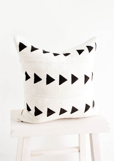 Square throw pillow in natural ivory mudcloth with black triangles printed in horizontal rows