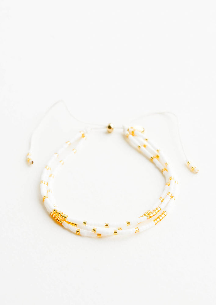 1: Beaded bracelet featuring three strands of white and gold glass beads and an adjustable sliding knot closure.