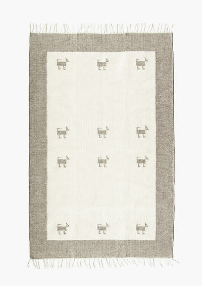 A wool rug with contrast border and light center with dog icons.