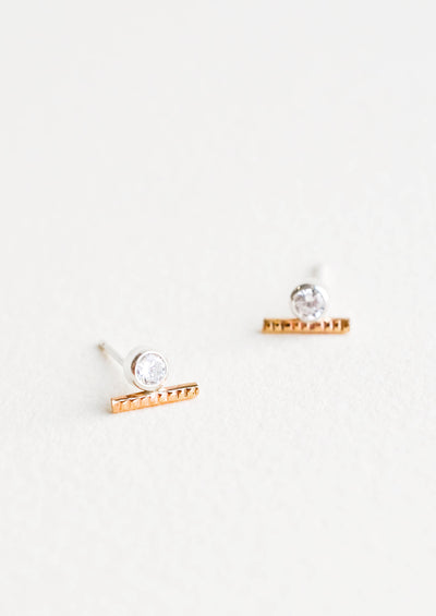 Stud earrings with a round white crystal set in a silver, attached to a short textured gold bar.