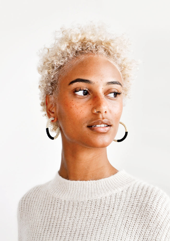 2: Model wears black and white beaded hoop earrings and white sweater.