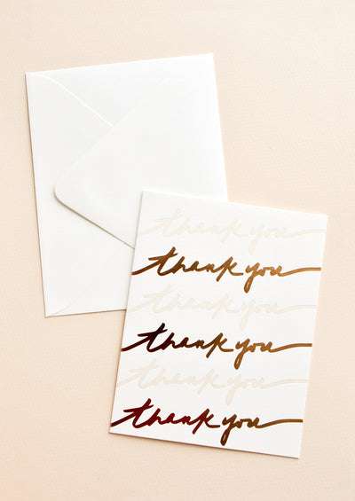 "Greeting card with alternating rows of ""thank you"" script in copper and white. Shown with white envelope."