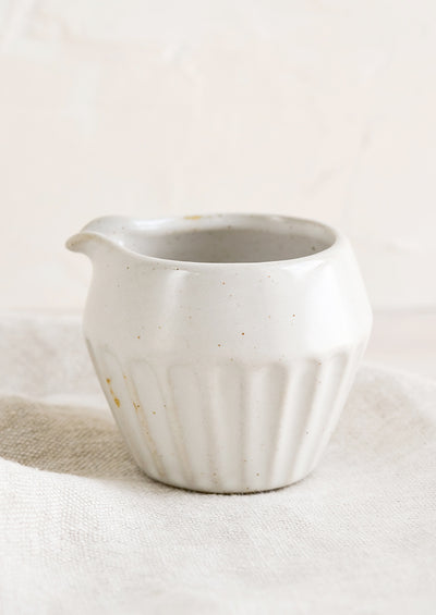 A small white ceramic creamer with ridged design.