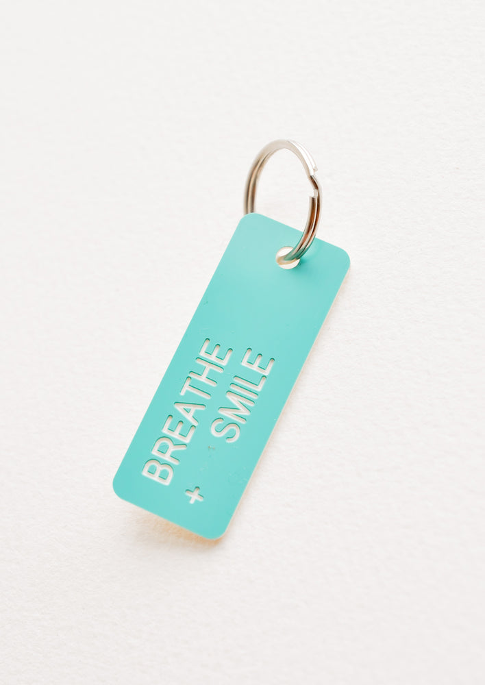 "Breathe + Smile: Small acrylic keychain, turquoise background with white words that says ""BREATHE + SMILE"""