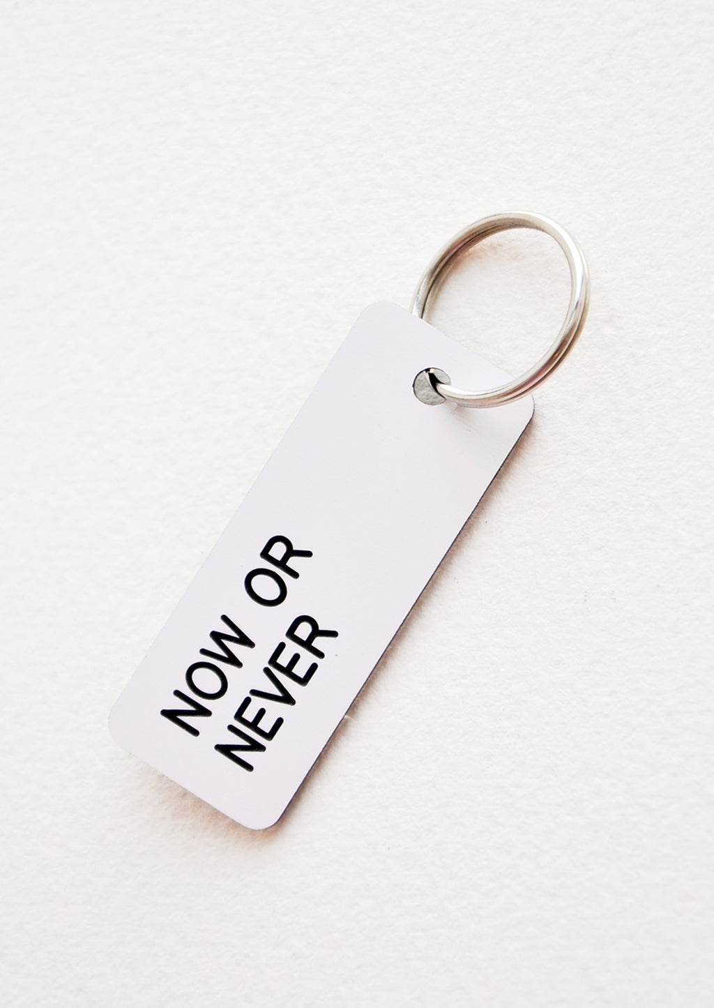 "Now or Never: Small acrylic keychain, white background with black words that says ""NOW OR NEVER"""