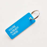 "You're Already There: Small acrylic keychain, blue background with white words that says ""YOU'RE ALREADY THERE"""
