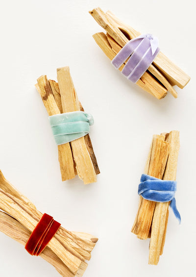 Four bundles of wooden sticks wrapped in red, green, purple, or blue velvet ribbon.