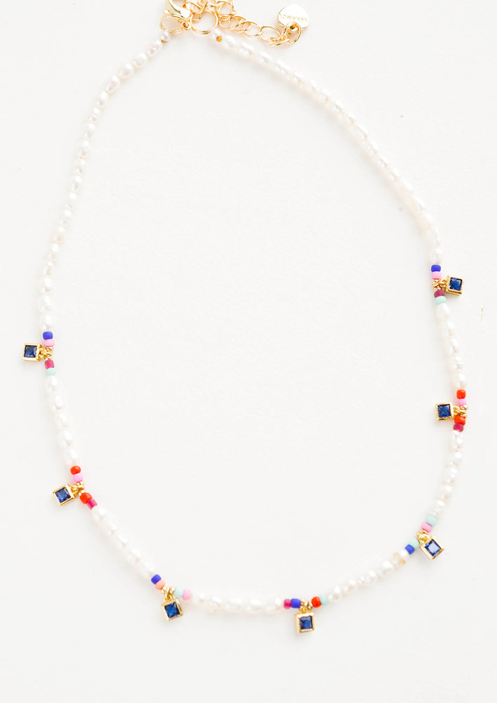 1: Beaded pearl necklace accented with square blue crystal stations and colored seed beads