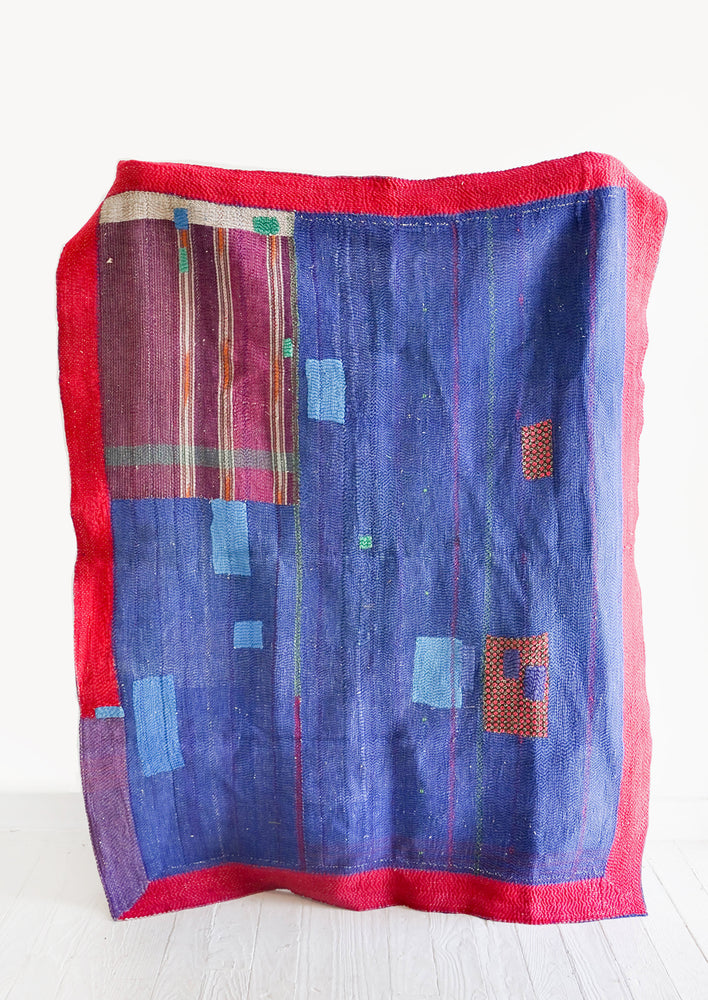 Vintage patchwork quilt in a mix of colors and fabrics. Predominantly dark blue with magenta accents.