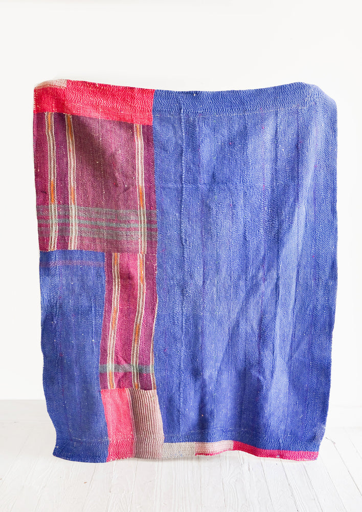 2: Vintage patchwork quilt in a mix of colors and fabrics. Predominantly dark blue with magenta accents.