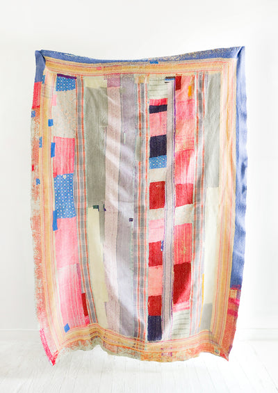 Vintage quilt with heavily patchworked design in blue, pink, red and various pastels