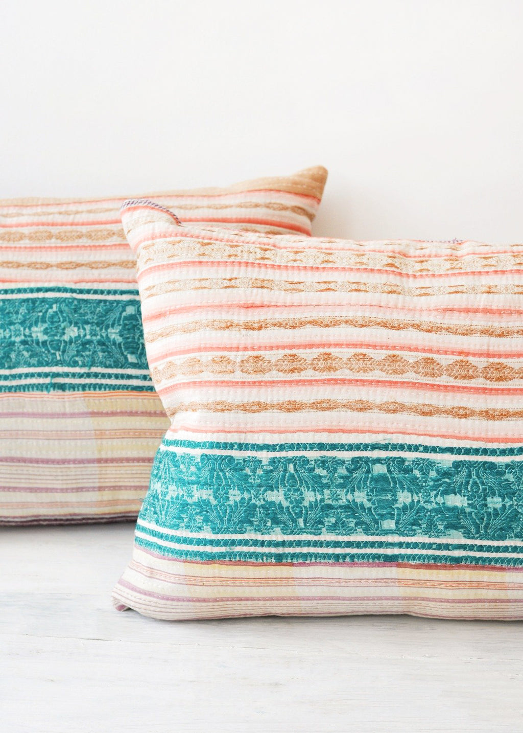 1: Two multicolored pillows made of vintage quilts.