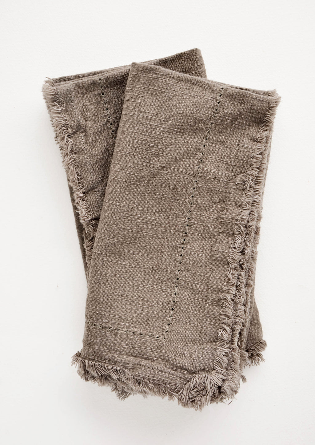 Fatigue: Two folded brown Cotton Napkins with frayed edges .