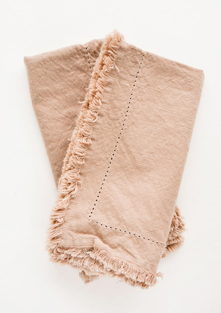 Cocoa: Two folded tan Cotton Napkins with frayed edges .
